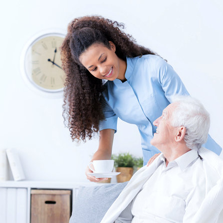 caregiver giving the senior man a cup of coffee