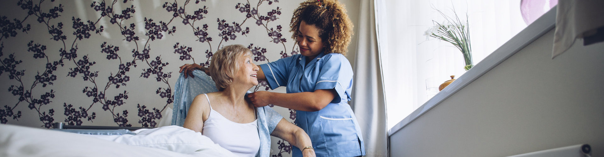 caregiver assisting the elder woman to dress up